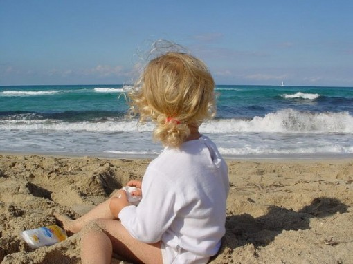 young girl sitting on beach in majorca