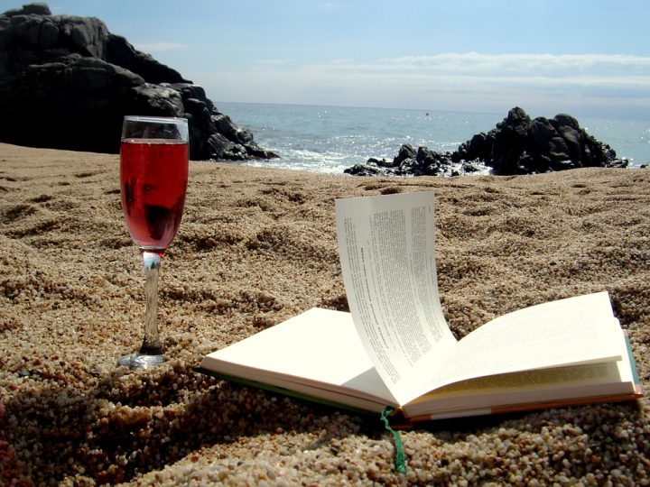 A glass of wine and a book on the beach