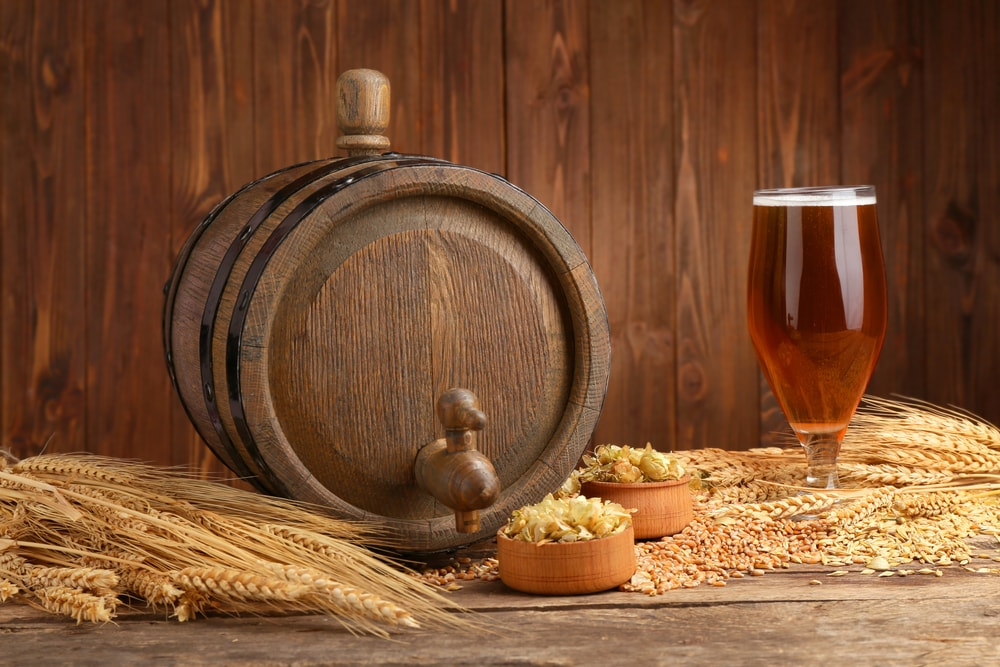 Beer barrel with hops and barley on wooden background