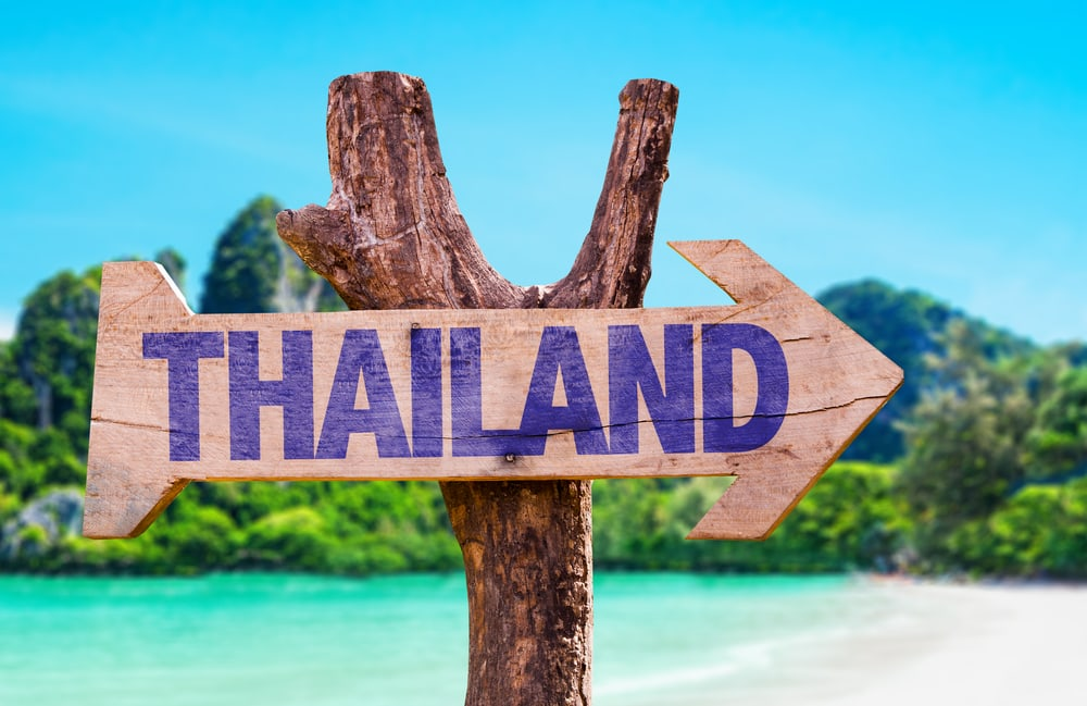 A wooden arrow sign that says Thailand