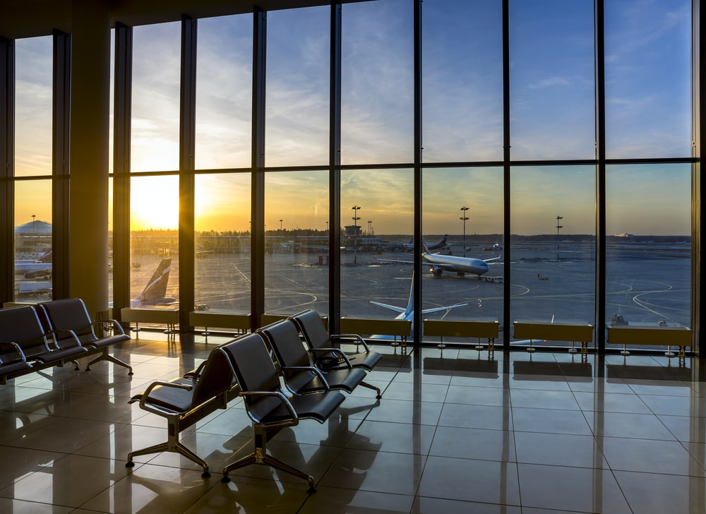 Silhouettes of bench in interior in airport lounge on background of the airfield with passenger planes