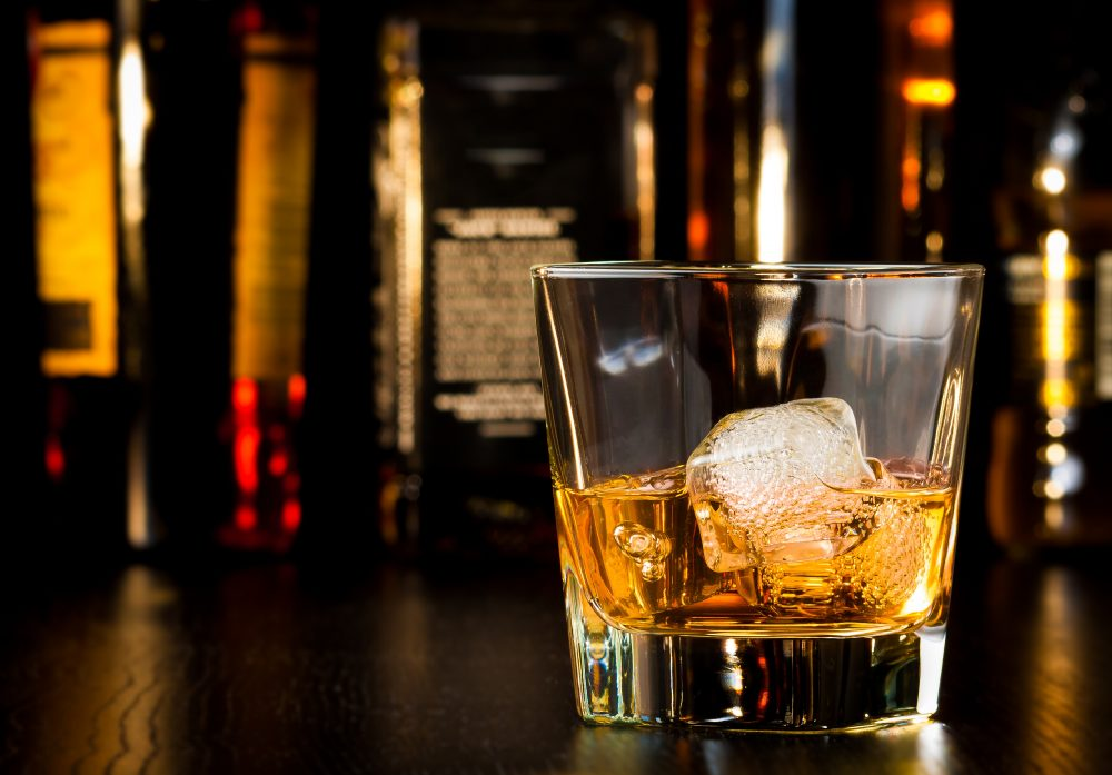 A glass of whiskey on the rocks on a dimly lit bar to celebrate world whiskey day.