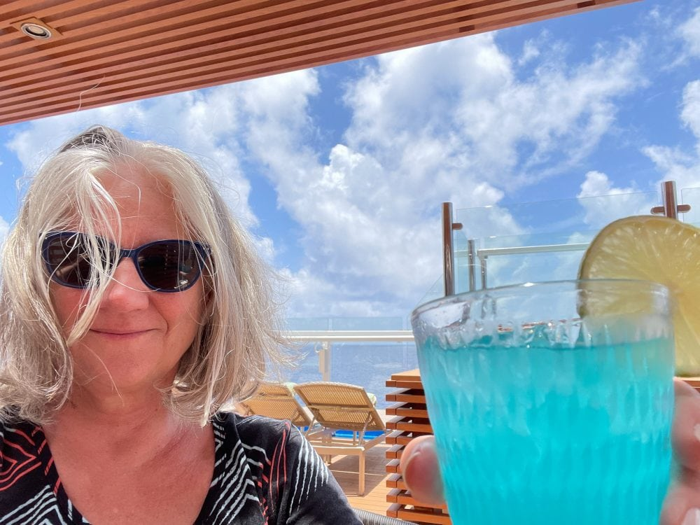 a woman holding a blue tropical drink
